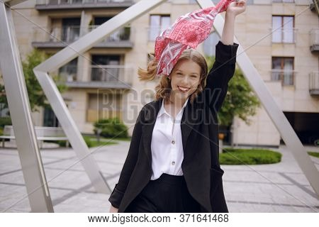 A Girl In A Business Suit With A Red Scarf On Her Head Against The Background Of A Building, Turns T