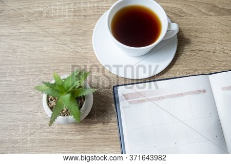 Top View Of Home Office Desk. Calendar, Diary Book, Meeting Agenda, Cup Of Coffee And Cactus Place O