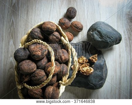 The Whole Walnuts Are  Into A Wicker Basket Next To Walnuts Broken On The Stone On Wooden Table. Org