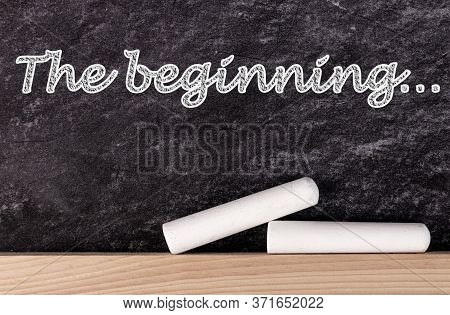 The Beginning Text On Blackboard With Two Pieces Of Chalk.