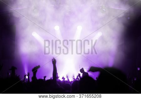 Silhouette Of An Emotional Crowd At A Music Festival In Front Of A Floodlit Stage