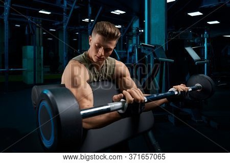 Bodybuilder In Sportswear Training Biceps With Barbell On Bench, Looking At Arms. Close Up Of Muscul