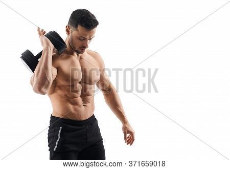 Shirtless Tensed Male Bodybuilder Holding Dumbbells On Shoulder, Looking Down. Portrait Of Man With