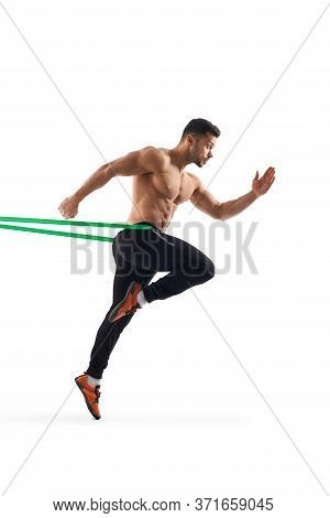 Side View Of Shirtless Bodybuilder Running In Place Using Resistanve Band. Muscular Man With Perfect