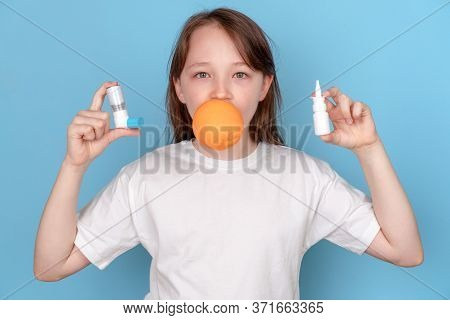 A 10-year-old Girl Holds An Orange And Allergy Pills In Her Hands. The Face Is Closed. Allergy To Fo