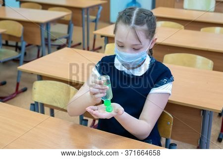 Close-up Face Of A Girl Schoolgirl In A Medical Mask Holds Antiseptic In Her Hands For Disinfecting