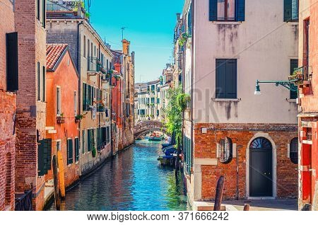 Venice Cityscape With Narrow Water Canal With Boats Moored Between Old Colorful Buildings And Stone