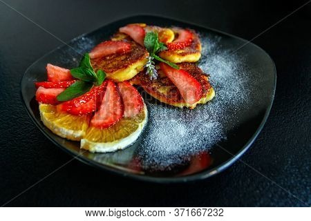 Tasty Cheese Pancakes With Slices Of Orange And Strawberries Decorated With Fresh Mint And Icing Sug