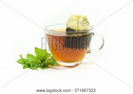 Healthy Hot Drink, Herbal Tea Bag In A Glass Cup And A Few Fresh Peppermint Leaves Isolated On A Whi