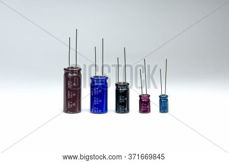 Close Up Of Electrolytic Capacitor Row With Various Sizes On White Background