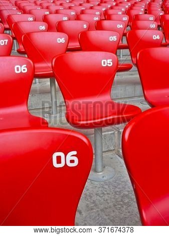 Red Fiber Glass Seating Chairs With The White Number And Amphitheater In A Ring Dome Arena Of Sports
