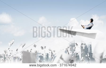 Aviator Driving Paper Plane Above Business Center In Blue Sky. Working With Business Documentation.