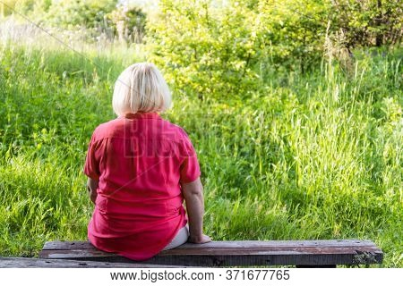 Lonely Adult Woman Back In A Pink Shirt Sits On The Bench In A City Park.