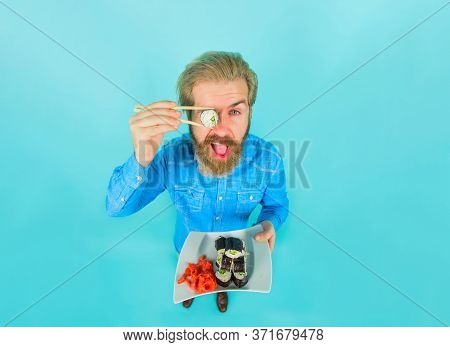 Man Eating Sushi. Bearded Man With Plate Of Sushi. Man With Sushi On Chopstick. Japan. Sushi Deliver