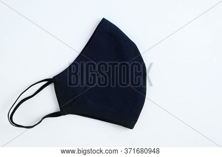 Protective Black Reusable Cotton Mask Folded In Half On A White Background. View From Above.