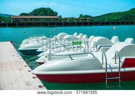 Row Of White Catamarans Standing On The Lake. Catamarans Near The Pier In Sunny Weather.
