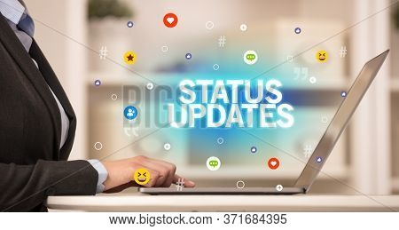 Freelance woman using laptop with STATUS UPDATES inscription, Social media concept