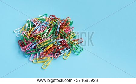 Colorful Paper Clips On Blue Background. Copy Space