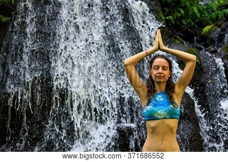 Hands Raising Up In Namaste Mudra. Yoga Near Waterfall. Young Woman Meditating, Practicing Yoga And