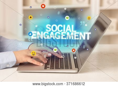 Freelance woman using laptop with SOCIAL ENGAGEMENT inscription, Social media concept