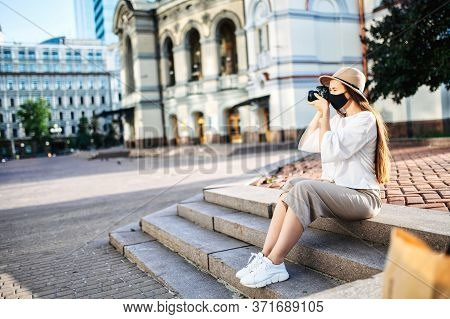 Young Woman Tourist Sightseeing. Girl With A Medical Mask On Her Face Takes A Photo While Sitting In