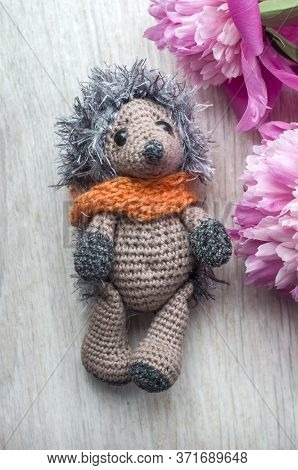 Crocheted Hedgehog With Pink Peony Flower On Wooden Background. Handmade Toy