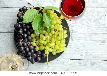 A Cluster Of Dark And Green Grapes And Two Wine Glasses With Red And White Wine On A Black Round Pla