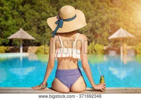 Back View Of Stylish Woman Is Relaxing, Sunbathing, Sitting Near Pool. Fashionable Girl In Swimsuit,