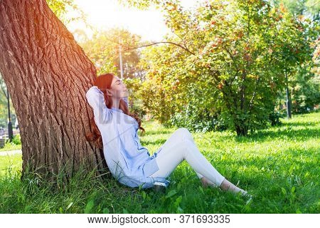 Young Woman Sitting Under Tree In Summer Park On Sunny Day. Beautiful Redhead Girl Relaxing With Clo
