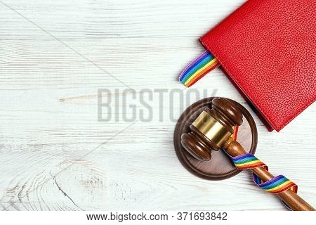 Judge's Gavel With Rainbow Ribbon And Notebook With A Lgbt Rainbow Bookmark On Wooden Table. Lgbt Ri