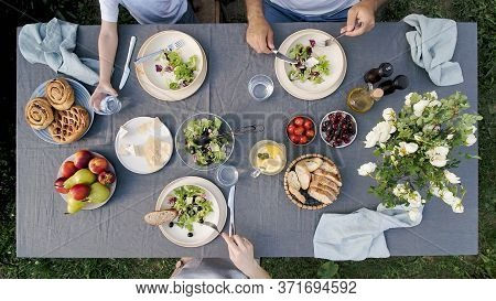 Family Dinner Outdoors. Family Dinner With Organic Salad And Cheese On Trendy Scandinavian Style Tab