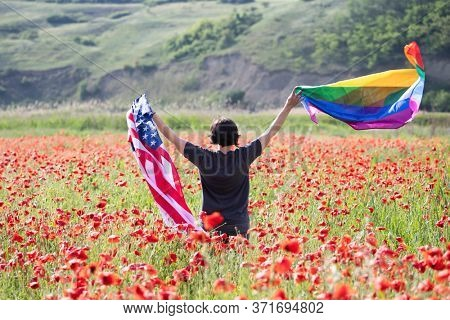 Woman holding LGBT and USA flag in poppy field. Gay equal rights and LGBT sexual freedom in America concept. LGBTQ community advocates for tolerance towards gender, sexuality and identity