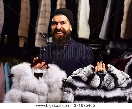 Shop Assistant Holds Grey Sable And Striped Chinchilla Fur Coats.
