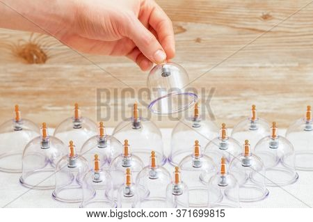 Hand Taking Vacuum Massage Glass Jar From Medical Set Of Traditional Chinese Cupping Therapy. Cuppin