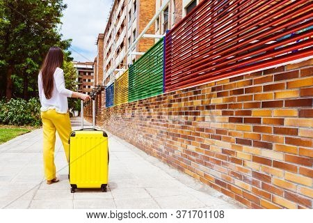 Woman On Her Back With A Yellow Suitcase Waiting On The Street