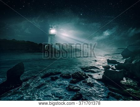 Picturesque Night Coast. The Glow Of The Lighthouse Against The Starry Sky.