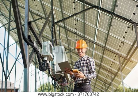 Smiling Man Engineer Checking The Operation With Laptop And Sensor, On The Background Of The Solar P
