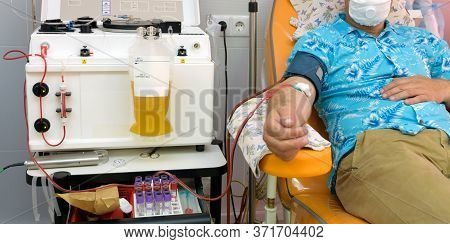 A Donor In An Armchair Donating Blood At Hemotransfusion Station