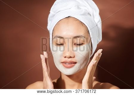 Young Asian Woman Applying Clay Mask On Her Face.