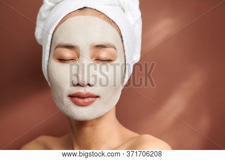Portrait Of Young Asian Wearing Clay Mask Over Brown Background.