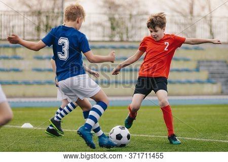 Children Kicking Football Ball. Boys Play Soccer On Grass Field. Stadium Tribune And Seats In The Ba