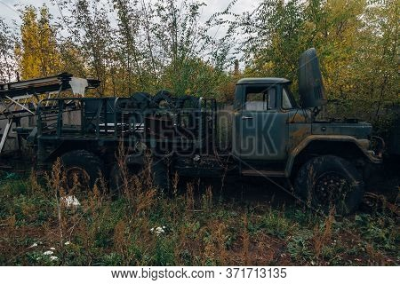 Old Rusty Truck At Abandoned Overgrown Industrial Area