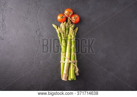 Concept Of A Bunch Of Asparagus And Cherry Tomatoes In The Form Of A Flower On A Dark Background. To