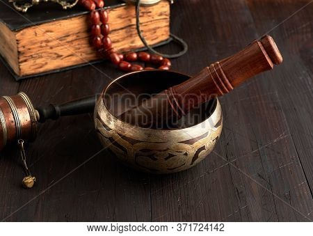Tibetan Singing Copper Bowl With A Wooden Clapper On A Brown Wooden Table, Objects For Meditation An