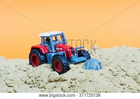 A Red Toy Wheeled Tractor In The Sand Next To A Coin With A Ruble Symbol. The Ruble Will Soon Be Rak