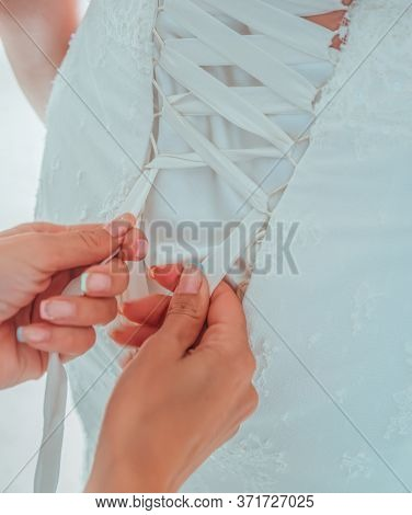 Morning Preparation Of The Bride. Closeup Of Bridesmaid Tying Bow On Brides Wedding Dress. White Rib