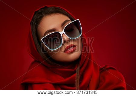 Portrait Of Chic Brunette Woman With Luxurious Make-up In White Sunglasses And Red Headscarf On Red