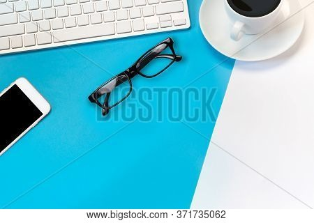 Flat Lay Office Desk Table Of Modern Workplace With Laptop On Blue And White Background, Top View La