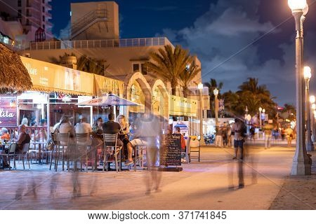 Hollywood Beach, Fl, Usa - June 26, 2020: Tourism On Hollywood Beach Fl Night Photo Tourists Sitting