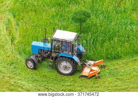 Tractor Uses Trailed Lawn Mower To Mow Grass On City Lawns, Aerial View